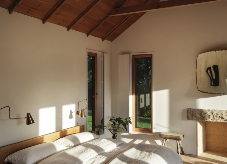 The main bedroom has four exposures, plus the original paneled ceiling and wood shutters.