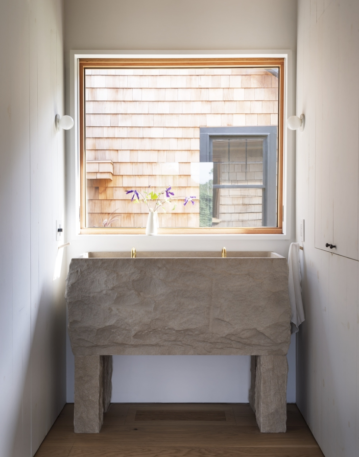 The primary bathroom features a rough-hewn limestone sink and brass Vola taps.