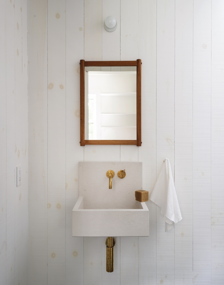 In the guest bath, an Elm Mini basin sink from Kast Concrete is paired with a midcentury Danish mirror.