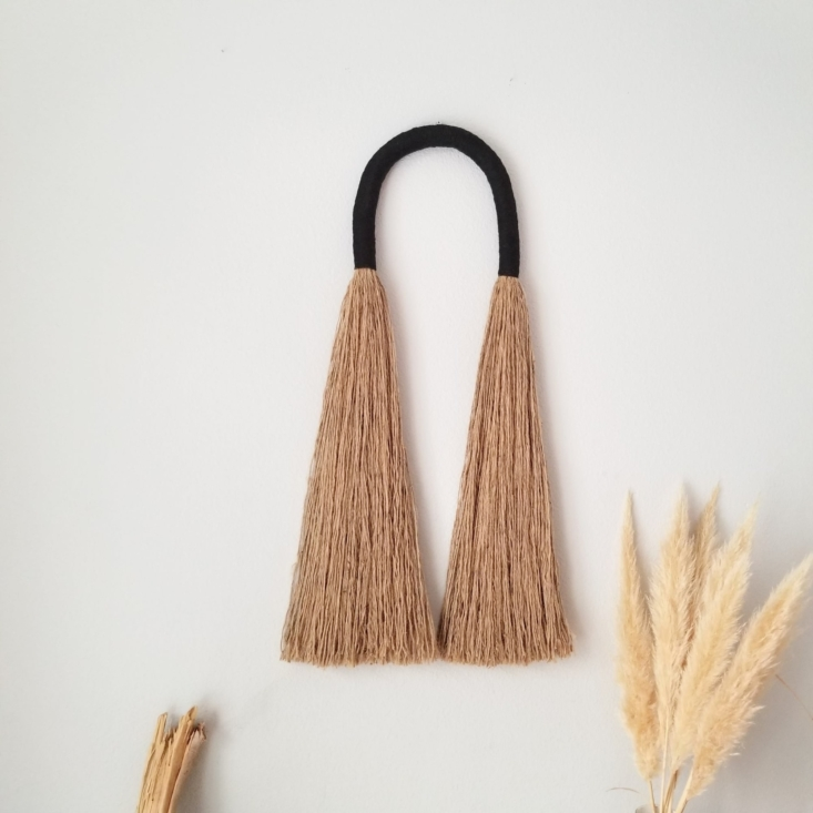 """Something for Every Wall Artful Pieces by Independent Makers on Wescover Reminiscent of a rustic hanging broom, the textural Large Arcus (\$340) is made from jute rope and black cotton rope to textural, """"untamed"""" effect. It's by macrame and fiber artist Yashi Designs and made in the US."""