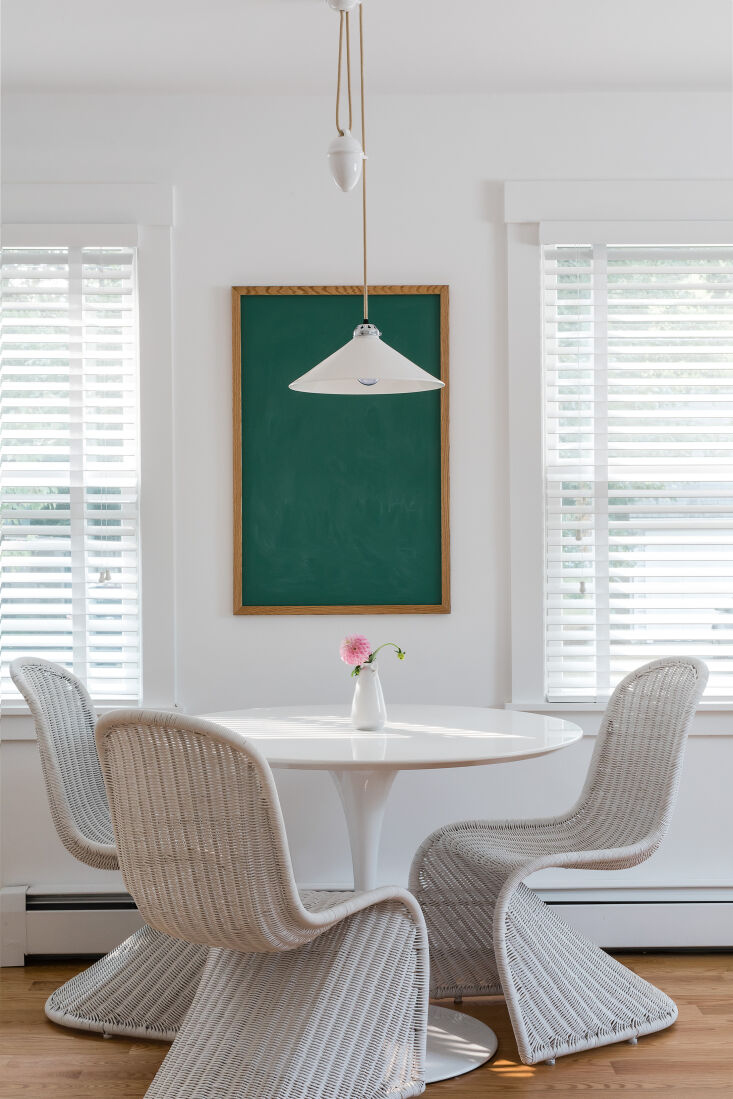 A Petite 1901 House in Concord MA Redone by a Former Magazine Creative The new dining area: a tulip table and wicker chairs tucked casually into the kitchen. A high/low moment: The light is the Cobb Rise & Fall Pendant from Original BTC and the &#8\2\20;art&#8\2\2\1; is actually a blackboard from a restaurant supply store.