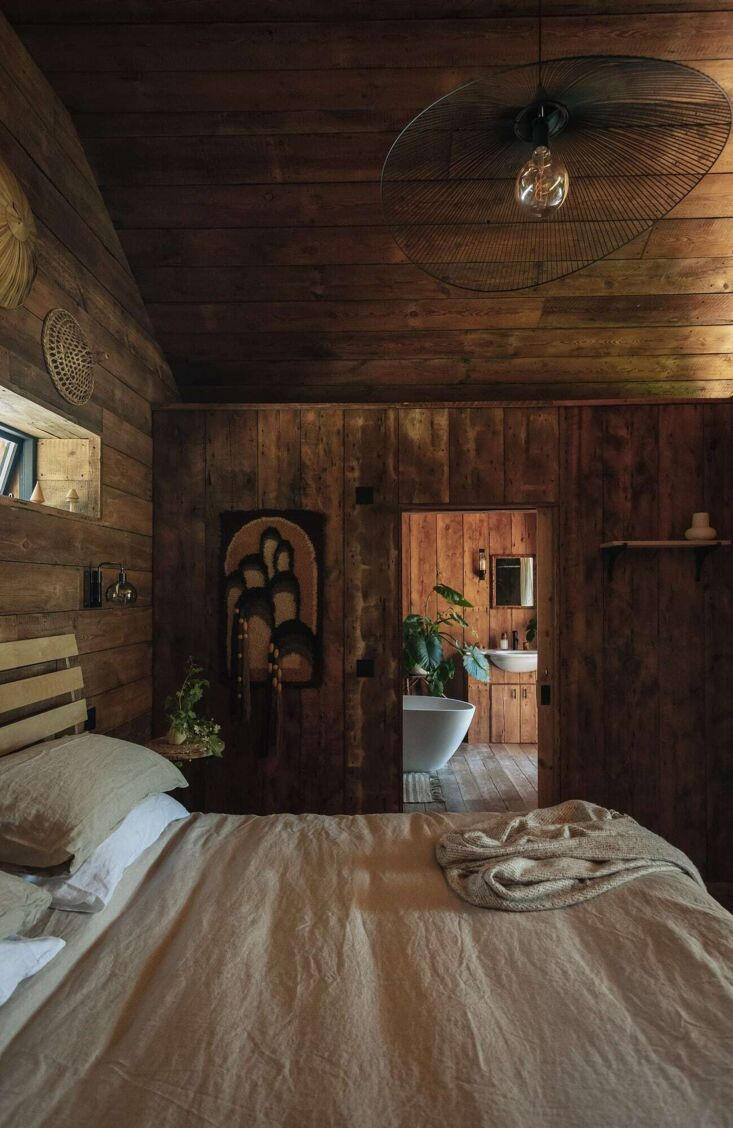 Retreat for Two A Lakeside Rental Cabin at Settle in Norfolk England The paneling continues in the bedroom—horizontal on the gable end, vertical everywhere else. The linens on the king size mattress are from Piglet in Bed.