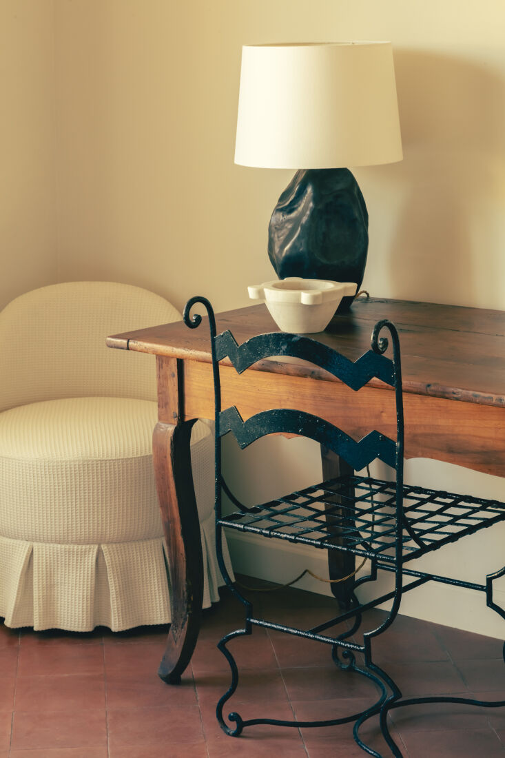 a wrought iron chair and vintage table in a guest room. 21