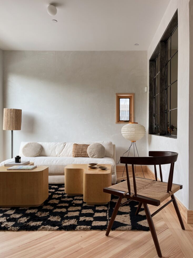 the sitting area is furnished with a cb\2 sofa and madeline weinrib rug from ab 26