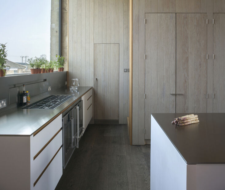 the cabinets and kitchen island are clad in corian and topped with brushed stai 11