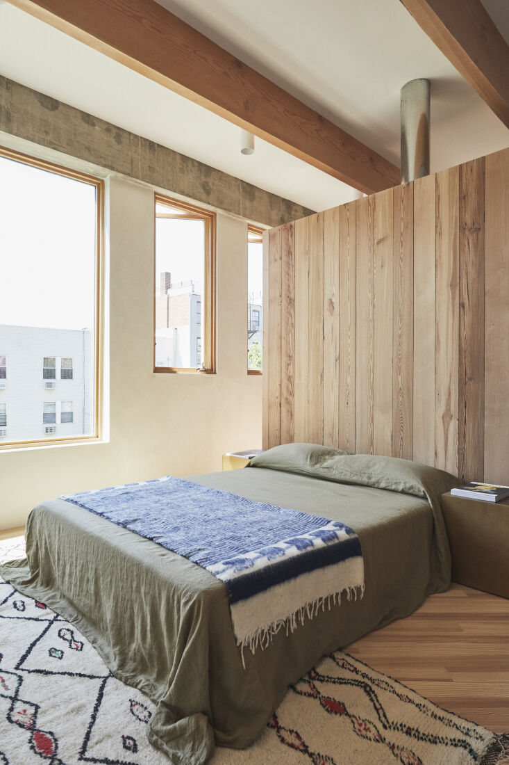 the bedroom is sectioned off from the closet by a paneled wood divider—a comb 19