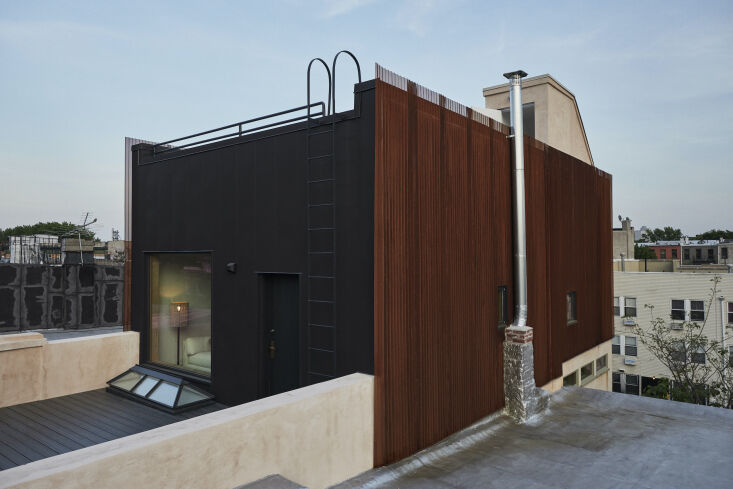 the top floor is clad in black corrugated steel and a weathered steel rain scre 27