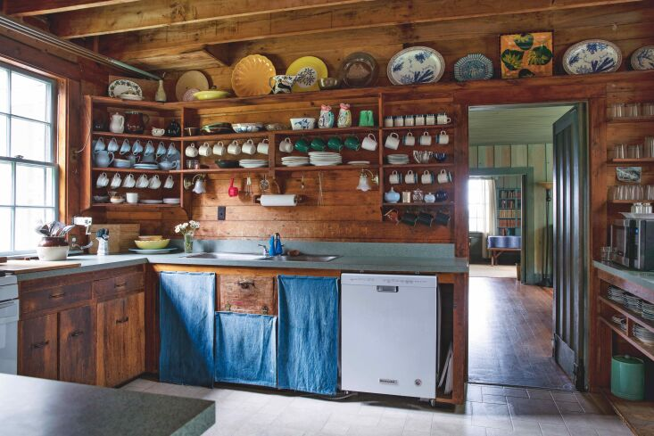 the wood clad kitchen is fitted with ad hoc cotton curtains in lieu of cabinet  13