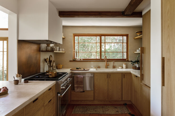 the kitchen is a warm material mix of oak, marble countertops, and copper fixtu 13