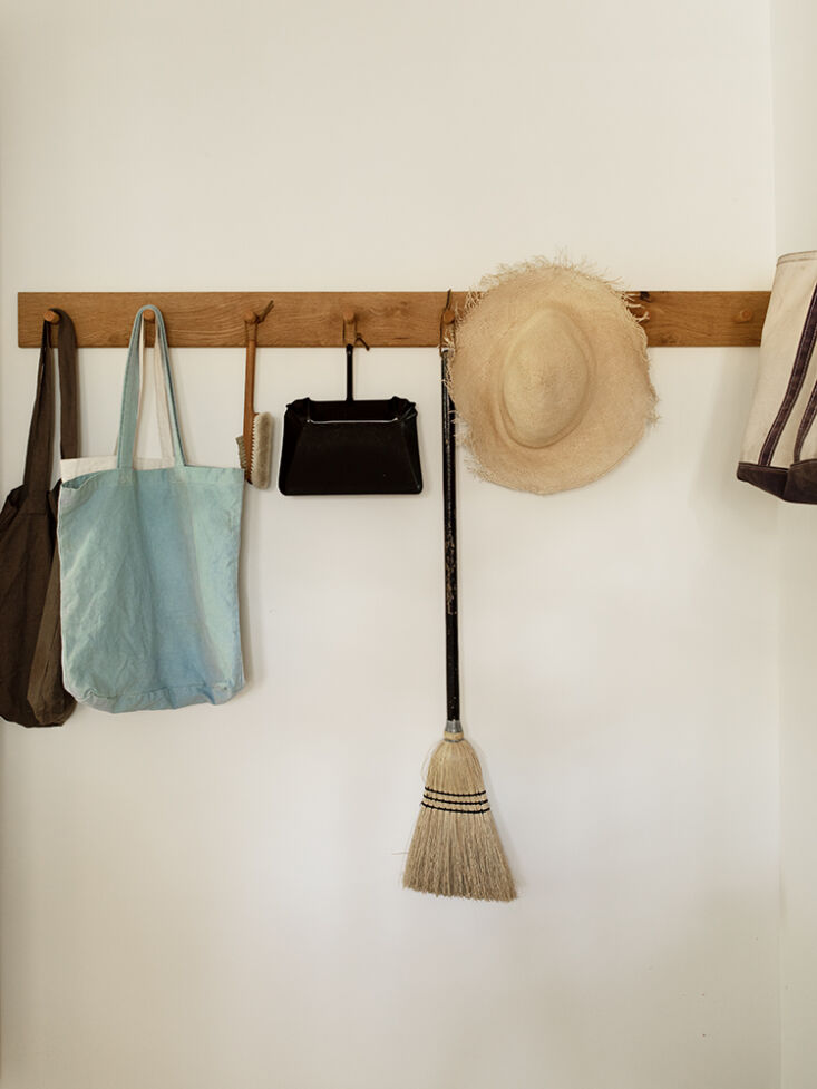 ease of living: brooms, bags, and summer hats are corralled on one of many peg  20
