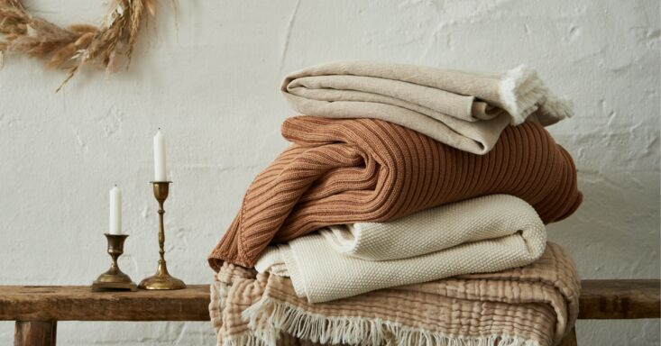 a stack of the brand's soft, textural blankets and throws in neutral, warm hu 14