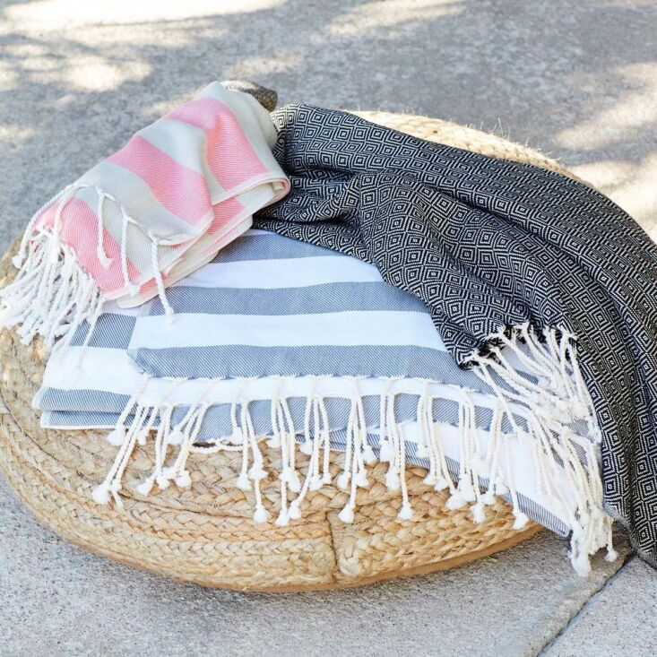 the filizhammam towel in dark blue and white (center, \$35)and the cesme ha 16
