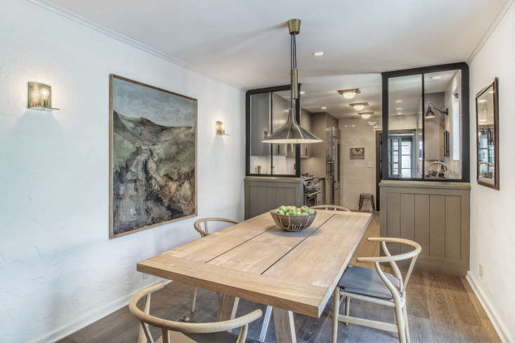 A vintage Danish pendant hangs above a teak farmhouse table with Wegner chairs. The large landscape painting is from Denmark. The windows behind offer a view into the kitchen.&#8
