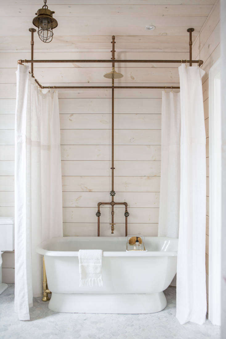 An antique soaking tub is ringed by custom linen shower curtains hanging from a brass-pipes shower curtain hoop designed by Anthony.